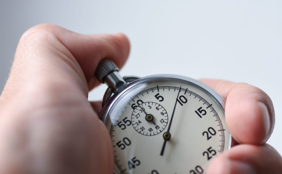A close-up of an isolated hand presses the stopwatch start button in the sport, measurements, metrology
